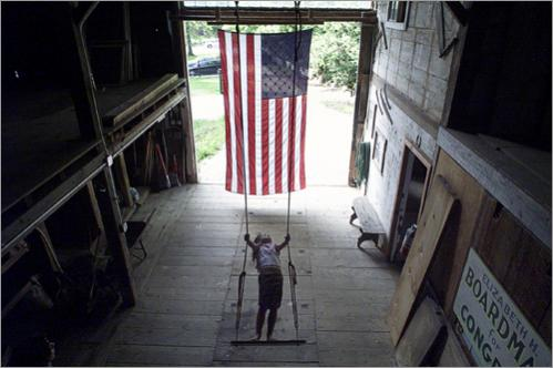 Buy this picture! Sophie Overall, 5, of Acton swings in her three-story barn. A giant ten foot flag hangs in the doorway. Her mother, Nina Overall, hung an antique wool flag she purchased at a yard sale ten years ago when she moved into this historic former 'Boardman House' a year and a half ago, but after Sept 11th she wanted to buy a sturdier, more permanent flag.