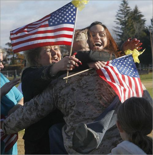 Buy photographs by Joanne Rathe Sgt. Brian Vitale is hugged by his mother Linda Bonanno-Vitale and his fiance Kaddie Gallant (right, with her feet in the air) during the homecoming for the 1st battalion 25th Marines. Vitale's sister Melissa is on the left.