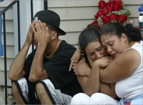 Buy photographs by Joanne Rathe From left, Omar Santiago, Joanna Rodriguez, and Julia Gonzalez mourn in front of a memorial for their friends, brothers Moises Cotto and John Tejada, who were shot on this porch at their home in Lowell in a drive-by shooting in 2004. Joanna had been a former girlfriend of Moises.