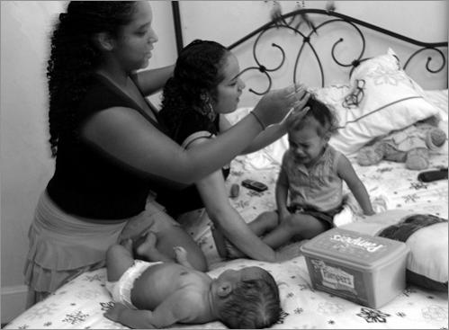 Buy photographs by Joanne Rathe Maria,17, left, helps her 19 year old sister Aida with Aida's two young children. Maria, one of 9 children, lives in foster care and is struggling to balance her own goals against the demands of her needy siblings.