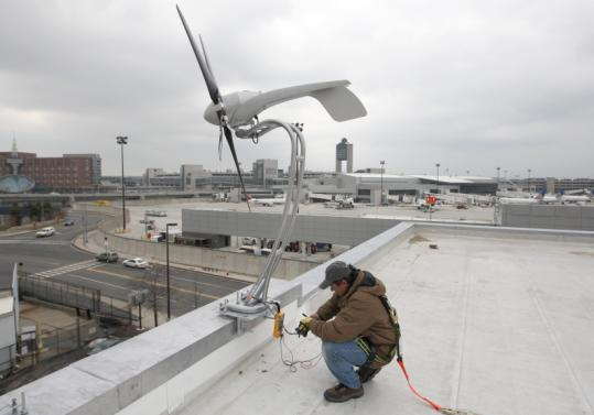 Jorge Andrade helped install five wind turbines yesterday on the roof of the Logan Office Center. About 100,000 kilowatt- hours are expected to eventually be produced annually by the array, which will number 20.
