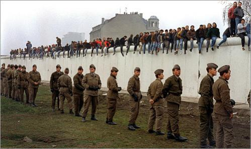 West Berliners line the Berlin Wall in 1989 as East German Soldiers still stand guard over an unopened section at Potsdammer Platz. This view is looking towards West Berlin. Adolph Hitler's bunker remains were found in this section of no-man's land which was mined and guarded by heavily-armed East German soldiers before the wall was opened.