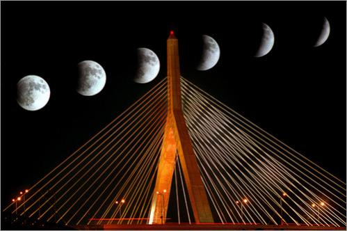 A 2003 total lunar eclipse is seen in an hour-long multiple exposure over the Leonard P. Zakim Bunker Hill Memorial Bridge. The eclipse is caused by the earth passing between the sun and the moon.