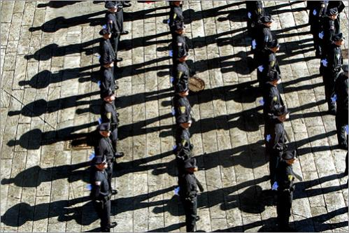 Police recruits line up outside Faneuil Hall as the morning sun casts their shadows. They wait to enter in formation for the Seventeenth Municipal Police Officer's Class graduation held inside in 2007.