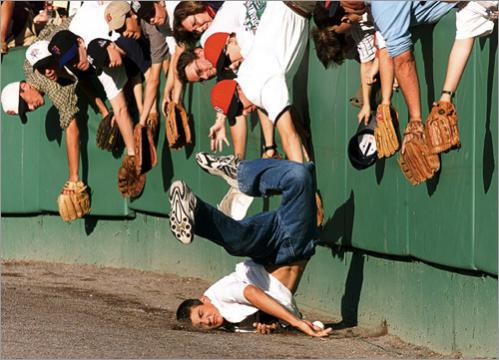 Before the start of the All Star game at Fenway Park in 1999, a zealous young fan beats his fellow amateur infielders to this batting-practice ball, but got a face full of dirt for his trouble.