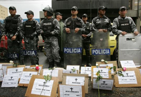 Ecuadoran police stood guard behind a memorial to victims of the Revolutionary Armed Forces of Colombia during a protest in Quito yesterday.