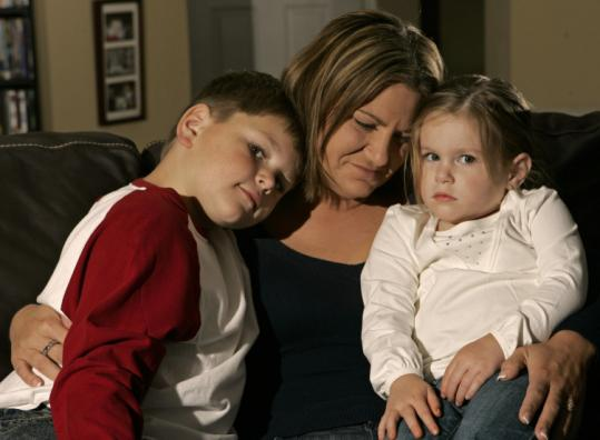Laura Youngblood with her children, Hunter and Emma, at their home in Sebastian, Fla. Youngblood's husband, Travis, a petty officer, died July 21, 2005, from wounds suffered in Iraq.