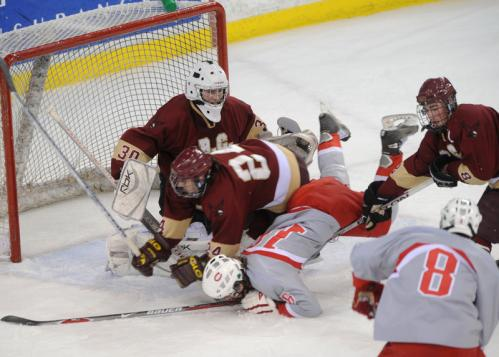 CM's T.J. O'Brien (16) is upended in front of BC High netminder Sam Marotta after he couldn't put his shot away with the Eagles' Brian Sullivan, center, and Tom Curran, right, converging in the crease along with CM's Benjamin Murphy (8).