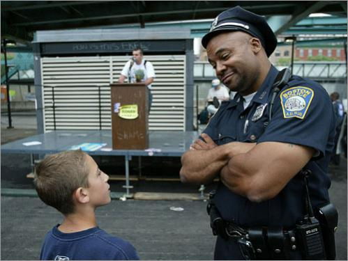Boston police officer Lawrence Welch, right, talks with his new friend John Franco, 11, in 2004 at the 'Free Speech' protest pen at the Democratic National Convention near the FleetCenter in Boston. Franco, whose mother works at a nearby restaurant, had wandered over to see what was happening in the area when officer Welch befriended him. The two spent a long time together talking, until the area became more active and Welch escorted Franco to a safer area.