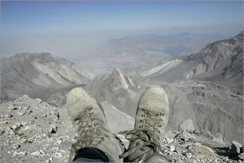 The hiking boots of photographer Mark Wilson frame the active section of a building lava dome in the volcanic crater of Mount St. Helens, visible after a hike up Monitor Ridge Trail. Mt. Rainier is visible on the distant right horizon.