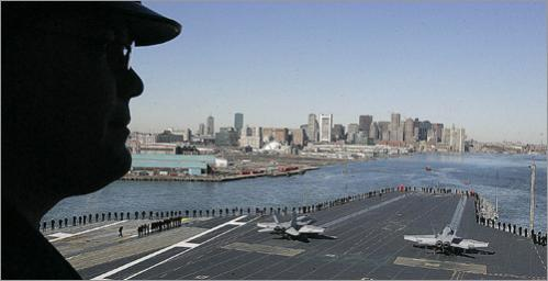 Lieutenant Dr. Geoffrey Wilson of the ship's medical company watches from near the bridge area as the USS John F Kennedy diesels into Boston Harbor in 2007.