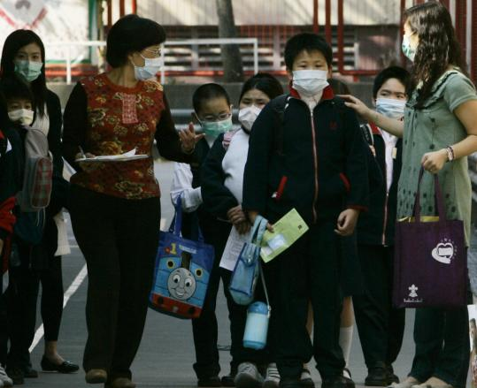 Students wearing masks as a preventive measure against flu lined up beside their teachers at a primary school in Hong Kong yesterday. Three children have died over the past week.