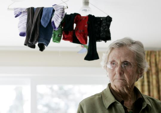 Mary Lou Sayer hangs her clothes from her dining room light in her Concord, N.H., home because her senior housing complex rejected her request to use clotheslines.
