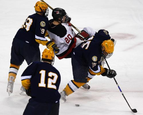 Xaverian defenseman Jameson Lee (19) upends Reading forward Rob Toczyloski (20) as teammate Andrew White (15) plays the puck.