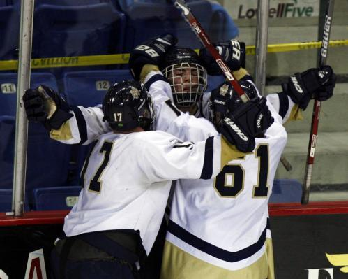 Malden Catholic players Zack Sheppard (17) and Mike Vecchione (61) celebrate with Greg Crovo after a second-period goal.