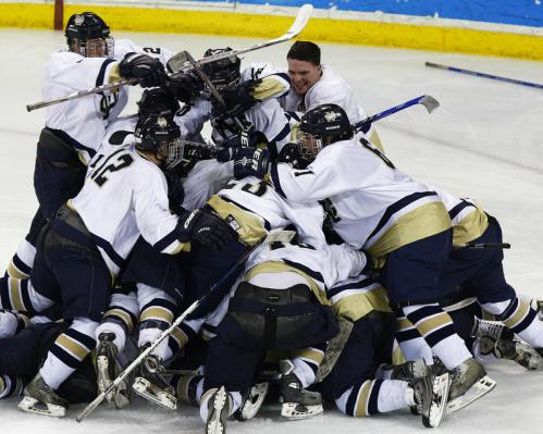 Malden Catholic players pile on one another as they celebrate their 3-2 win over Catholic Memorial.