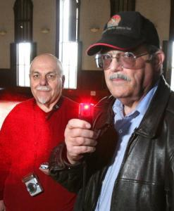 Paranormal investigators Len Anderson (left) and Ed Beaulieu with a handheld laser that can read temperature.