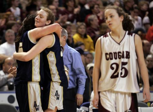 Archbishop Williams' Alex Knowles (left) embraces Valerie Driscoll near the end of the game as Quaboag's Brianna Flemming walks down the court.
