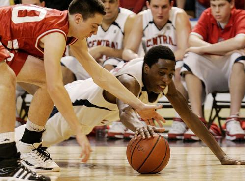 St. John's Brandon Russell (left) and Central Catholic's K.B. Oshodi dive for a loose ball.
