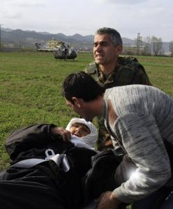 A relative comforted a wounded woman as she was evacuated yesterday by an Albanian army officer from the site of powerful explosions that occurred in Gerdec village Saturday.