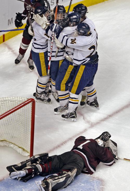 Westford Academy goalie Curtis Serafini (1) is down and out as Needham players surround Sam Kane as they celebrate the goal that put them ahead 3-0.