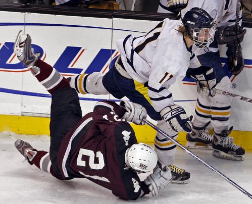 Westford Academy's Brian Milisci (21) falls to the ice courtesy of a hit from Needham's Will Rayner (11).