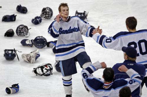 With the equipment discarded during the celebration littering the ice, Sandwich forward Andrew George shows off the championship medal he just received as his team downed Wilmington, 1-0.