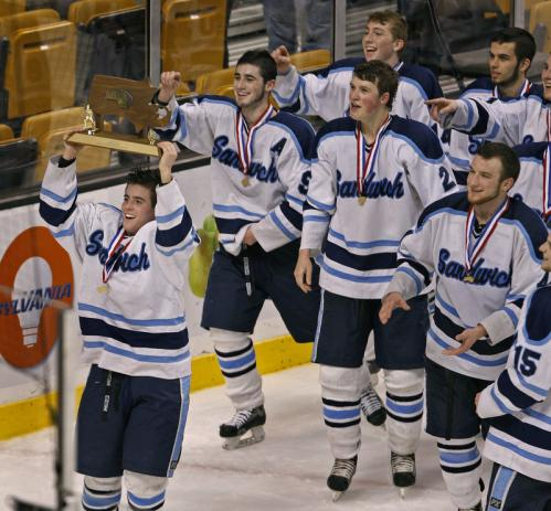 Sandwich's Garrett Lessard (left) leads his teammates as they celebrate with the state championship trophy following their victory over Wilmington.