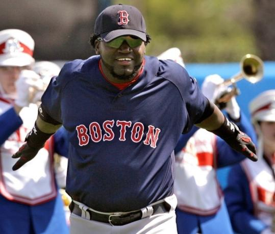 His swing is not yet making sweet music, but David Ortiz stretches yesterday with a marching band behind him.