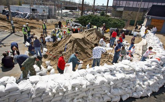 Volunteers piled sand bags around the Old Towne Fenton Veterinary Clinic in Fenton, Mo., yesterday. The rivers are expected to crest tonight after heavy rainfall.