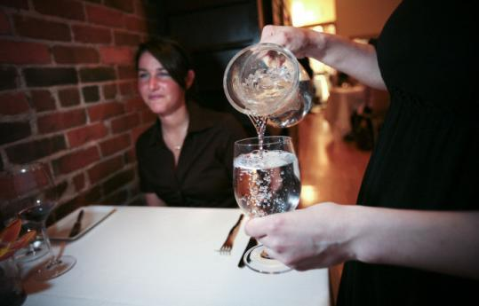 Lauren Grassetti received water Thursday at T.W. Food in Cambridge. Waiters offer glasses of 'Cambridge filtered.'