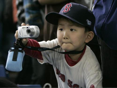 A Red Sox fan takes a photo before the season opener.
