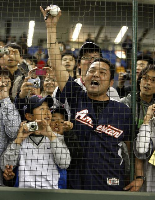 A fan yells for an autograph during the Red Sox warm-ups.