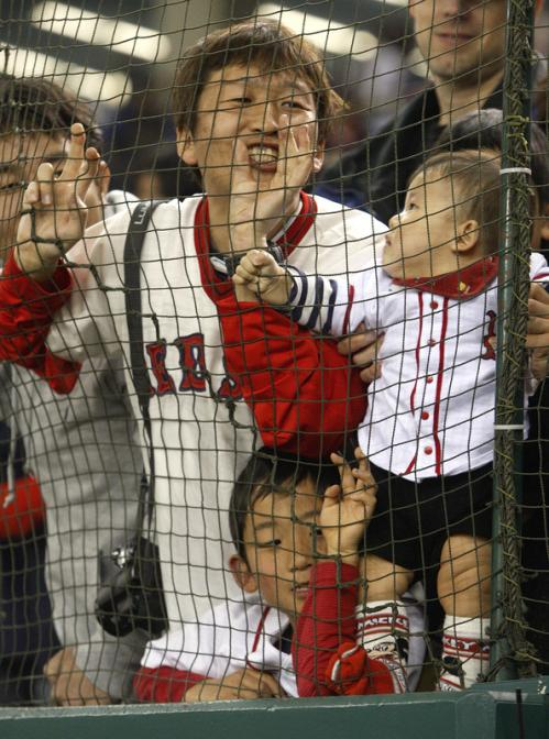 Red Sox fans yell to the players during the team's pregame warm ups.