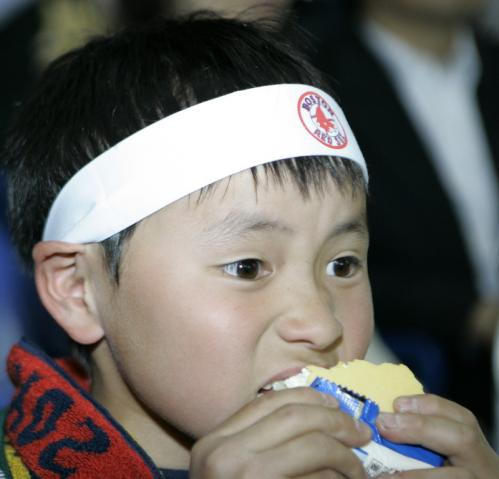 A young Boston fan wearing a headband with the team's logo eats ice cream during the season opener in Japan.