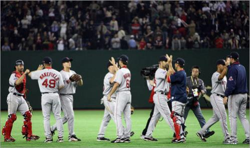Red Sox players celebrate after defeating the Oakland Athletics, 6-5 in the season opener.