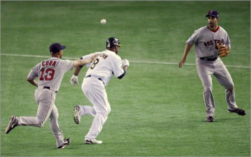 Oakland Athletics' Emil Brown (center) is chased by Alex Cora (left) and Mike Lowell after getting caught in a rundown in the 10th inning.