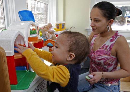 Anushka Ramirez, 18, plays with her 18-month-old son, Erik Santiago, at Ruth House, a nonprofit that helps homeless teenage mothers. The Brockton organization receives funds from Lutheran Social Services, which is paying attention to how the economy may affect giving.