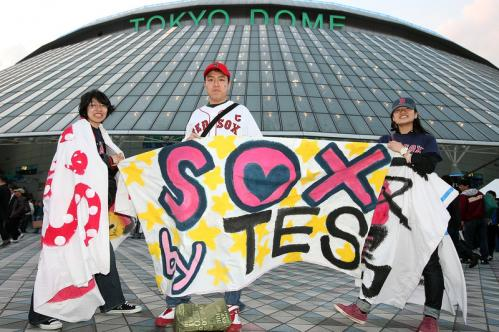 Red Sox fans pose in front of the Tokyo Dome before Game 2 of the Red Sox and Athletics series in Japan.