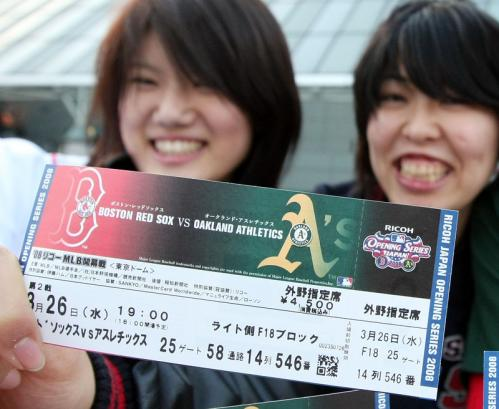 Japanese baseball fans hold a ticket to Game 2 between the Red Sox and A's.