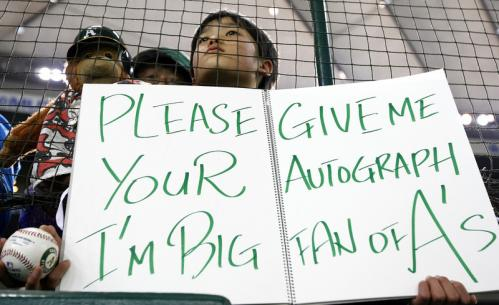 A Japanese fan looks for autographs from the Oakland Athletics.