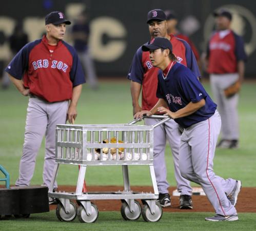Daisuke Matsuzaka pushes a cart to collect balls during warm-ups.