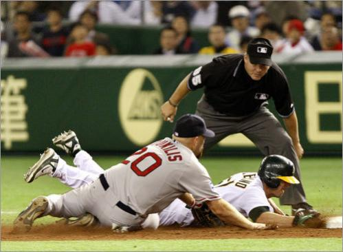 Oakland third baseman Jeff Fiorentino dove back into first, trying to avoid the tag by Boston's Kevin Youkilis.