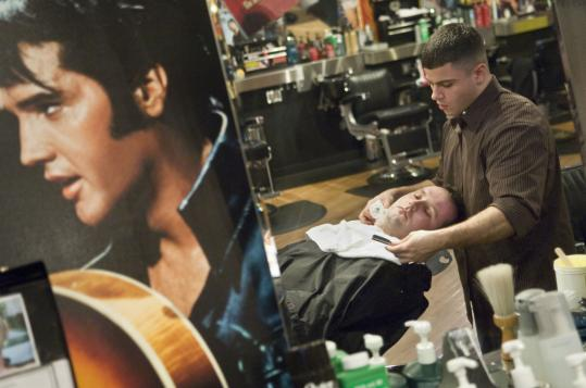 Chris Nieves shaves Andrew Hurley at Floyd's 99 Barbershop, one of the salons catering to men that have opened in the area.