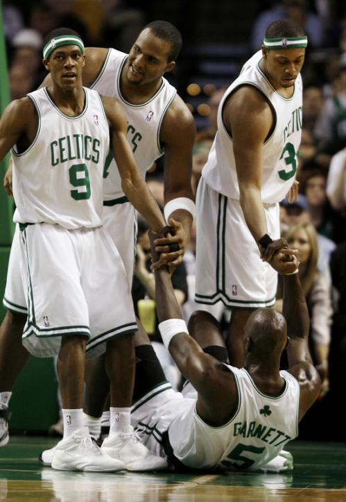 Rajon Rondo (9), Glen Davis, and Paul Pierce (34) help teammate Kevin Garnett (5) get back on his feet after being fouled.