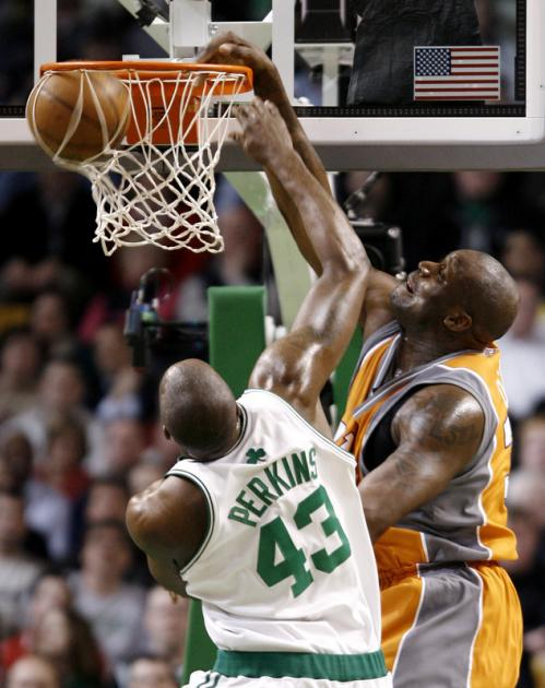 Shaquille O'Neal, right, dunks over Kendrick Perkins.