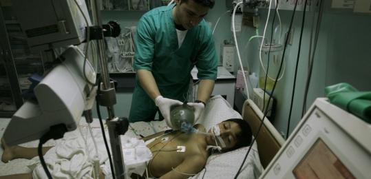 A Palestinian doctor tended to a patient in Gaza City yesterday. A leading health organization said dozens of Gaza residents have died after delays obtaining permits to enter Israel.