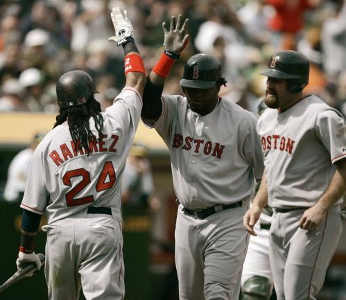 David Ortiz (center) is congratulated by teammates Manny Ramirez (No. 24) and Kevin Youkilis after Ortiz hit a two-run home run off the Athletics' Alan Embree during the seventh inning in the Red Sox 5-0 win in Oakland on Wednesday.