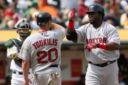 David Ortiz is congratulated by Kevin Youkilis after hitting a two-run home run during the sixth inning against the Athletics at the McAfee Coliseum.