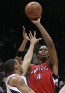 Toronto's Chris Bosh (24 points) shoots over Hawks' Acie Law, but Atlanta won.